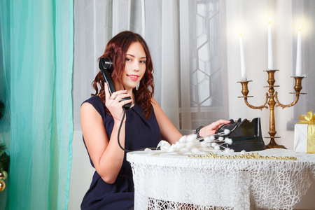 Portrait of attractive brown-haired woman indoors with retro phone
