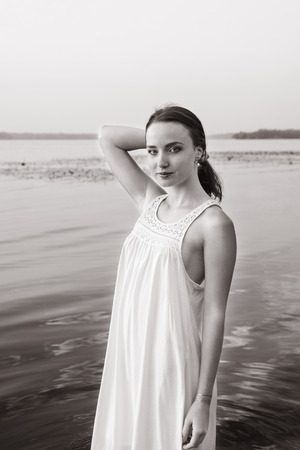 attractive girl in a white dress standing by the river at dawn. beauty, fashion, portrait.