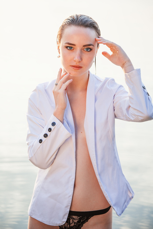 attractive girl in a white jacket stood by the river at dawn. beauty, fashion, portrait, outdoor. Stock Photo