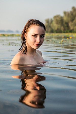 attractive girl on his shoulders in the river at dawn. beauty, fashion, portrait, outdoor.