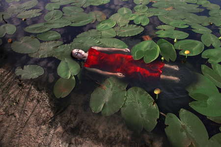 Soar in the water. Attractive sensual girl in water with water lily
