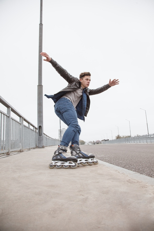 young attractive guy rollerblading in the park