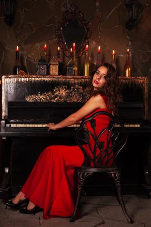 Beautiful brunette in red dress near piano