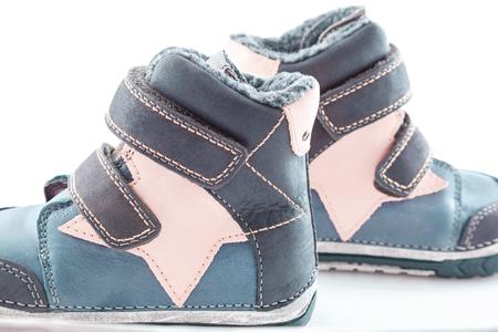 Zapatos de invierno elegantes y cómodos para niños sobre un fondo blanco.