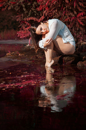 attractive girl in lingerie and white shirt is sitting on a rock by the river at dawn. beauty, fashion, portrait. Artstyle