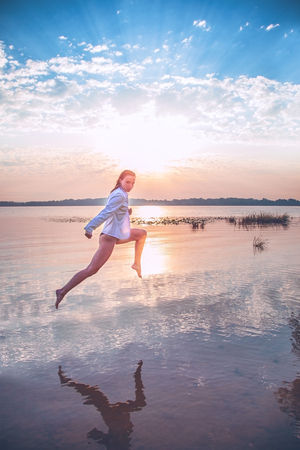 attractive girl in a white jacket is jumping over the water at dawn. beauty, fashion, portrait, outdoor.