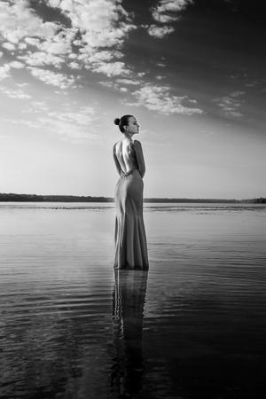 Jolie fille debout dans l'eau sur fond de beau lever de soleil. Beauté, mode, plein air, beaux-arts