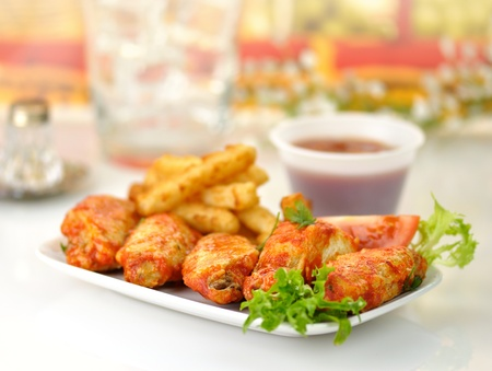 hot chicken wings with fried potatoes and sauce photo