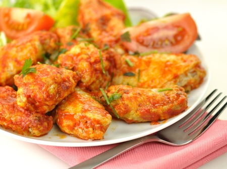 spicy: hot chicken wings with salad close up