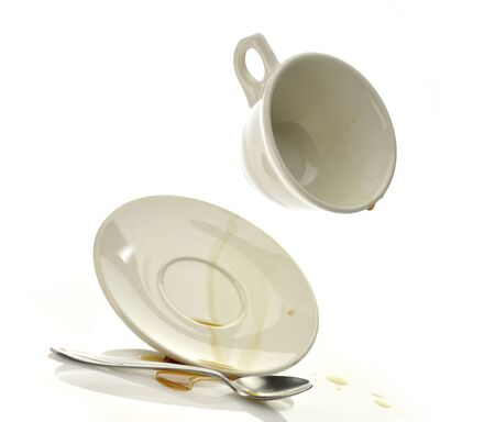 Kop en schotel met gemorste koffie Stockfoto