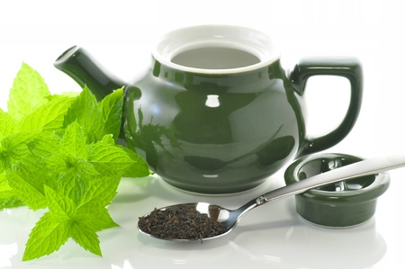 green teapot with mint plant and loose tea photo
