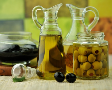 cooking oil:  bottles of olive oil with black and green olives