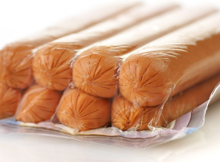 sausages in a plastic package on a white background, closeup photo