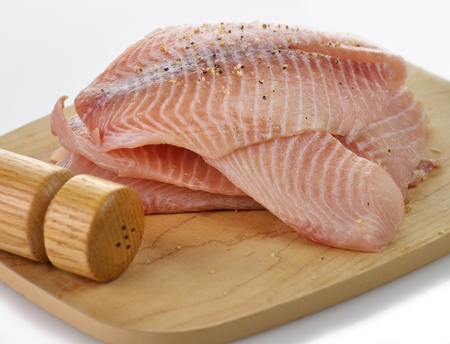 tilapia fillets on a cutting board with spices Stock Photo - 9312124