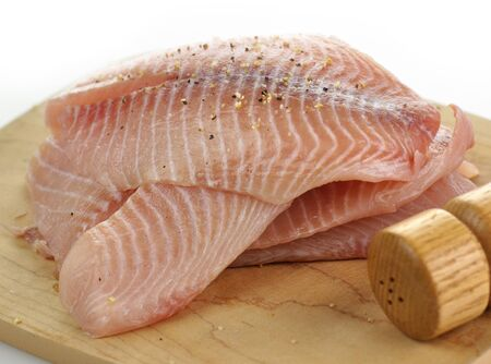 tilapia fillets on a cutting board with spices photo