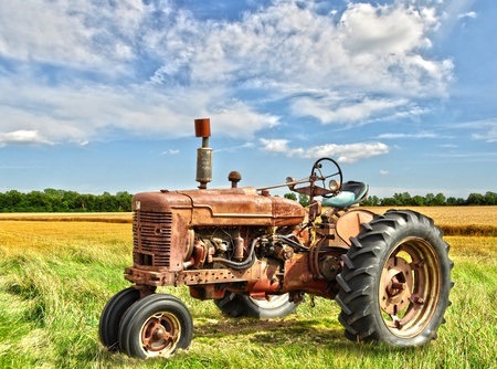 farm machinery: red old rusty tractor in a field