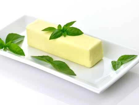 Butter stick on a white dish with basil leaves
