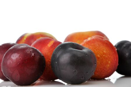 Juicy nectarines, plums and peaches on white background