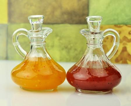 italian  and raspberry vinaigrette salad dressings in glass bottles photo