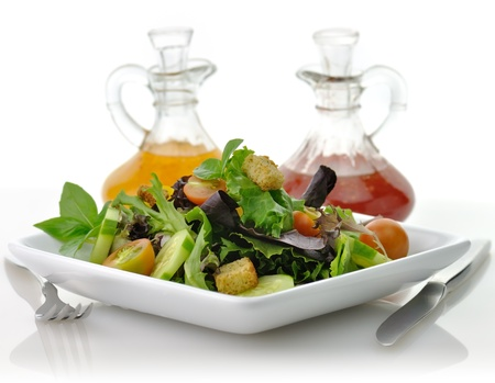 a fresh vegetable salad in a white dish with salad dressing