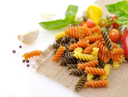 twists: Colorful pasta on white with tomatoes and spices Stock Photo