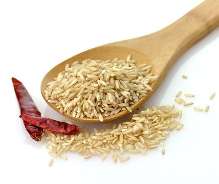 Natural brown rice in a wooden spoon  Imagens