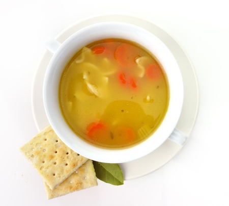broth: Chicken noodle soup in a white cup with crackers