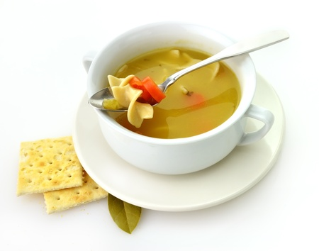 sopa de pollo: Sopa de fideos de pollo en una taza blanca con galletas