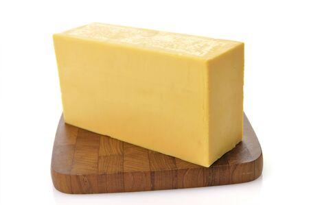 cheddar: A Bar Of Sharp Cheddar Cheese On A Cutting Board