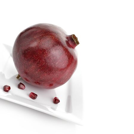 Ripe Pomegranate With Red Seeds On White Background