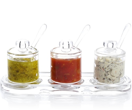 Various Dips In Glass Jars On White Background