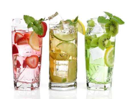 té helado: Vasos de bebida con cubitos de hielo y frutas en el fondo blanco