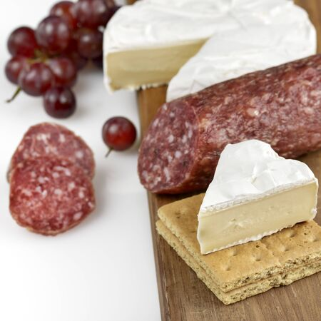 Brie Cheese And Salami On A Wooden Board