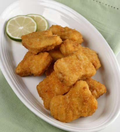 nuggets pollo: Oro Nuggets de pollo en un plato blanco