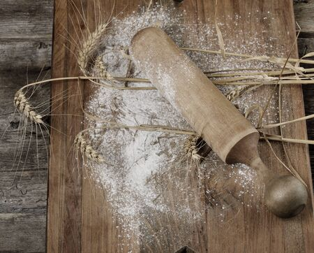 pin board: Wooden Rolling Pin, Flour And  Wheat On A Wooden Board
