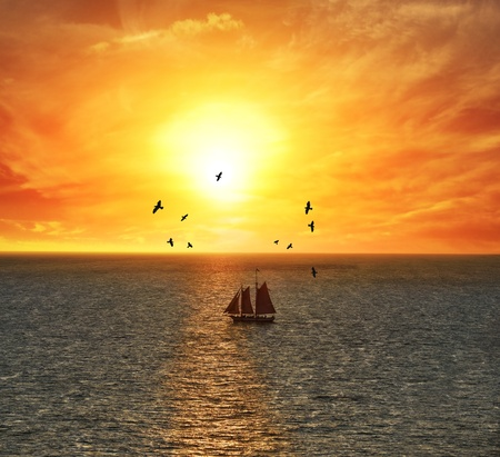seabirds: Sailing Boat At The Colorful Sunset Stock Photo