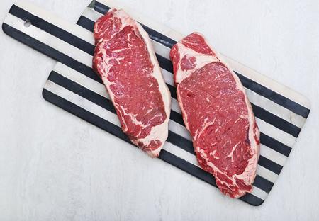 Raw new york strip steaks on a cutting board