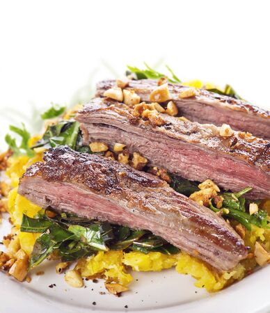 flank steak with mashed plantain , collard greens and ginger peanuts , close up