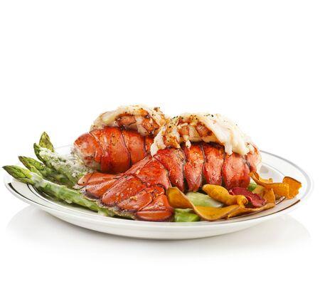 Queues de homard grillées servies avec des asperges sur fond blanc Banque d'images