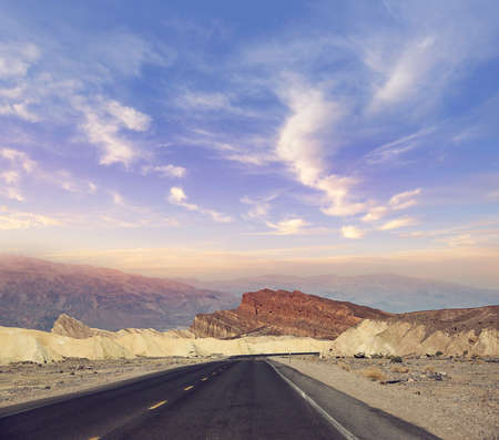 Desert road leading through Death Valley National Park at sunset , California USA. 写真素材