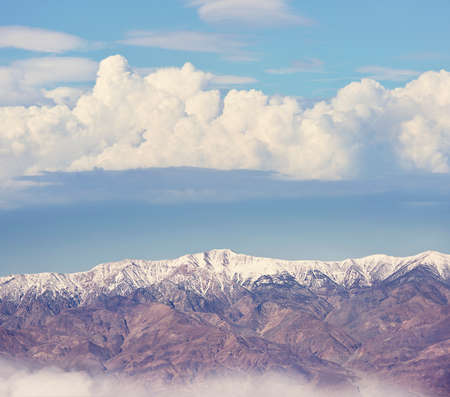 Snowy mountains with clouds on a blue sky 写真素材