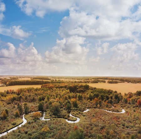 Beautiful countryside with a small river and autumn trees. Aerial landscape. 写真素材