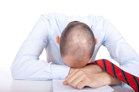 burnout: Studio shot of an exhausted business man putting his head on the desk Stock Photo