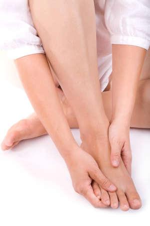 manos y pies: Studio foto de una mujer joven masajear su pie derecho Foto de archivo