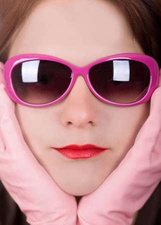 Retrato foto de una mujer joven con gafas de sol de color rosa