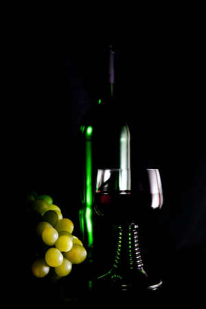 De bajo perfil plano de una botella de vino, una copa de vino y las uvas algunos