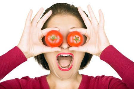woman open mouth: Young woman holding two tomatoes in front of her eyes Stock Photo