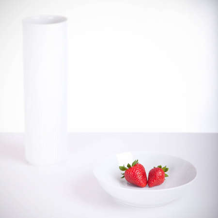 Studio shot of a bowl a vase and two strawberries