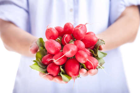 A young woman holding a bunch a radish