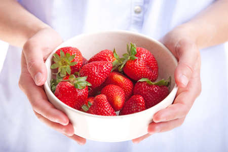 Young woman holding a bowl of fresh strawberries Stock Photo